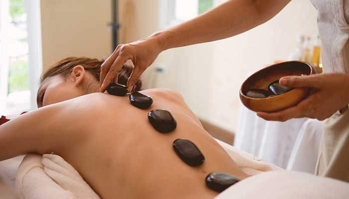 Woman enjoying a hot stone massage at the health spa