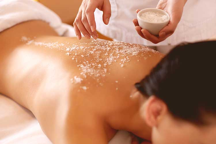woman getting salt scrub and oil massage